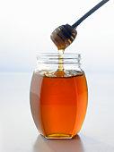 Honey dipper with jar of honey, close up