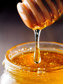 Honey dripping from honey-dipper in glass jar. Extreme closeup.