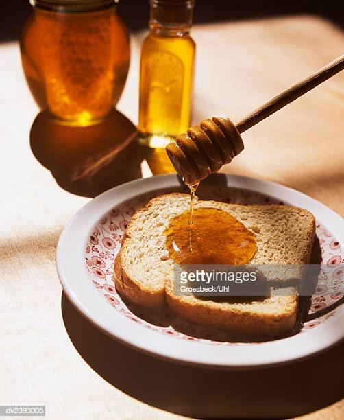 Honey Drizzler Dripping Honey On a Slice of Brown Bread