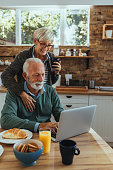 Cute mature couple using laptop