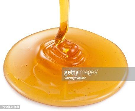 Honey flowing on white background. : Stock Photo
