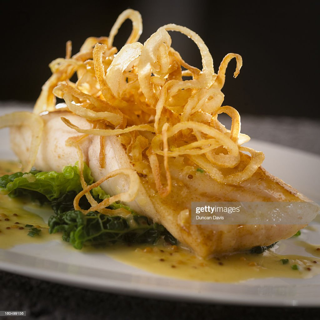 Honey glazed turbot in a mustard sauce with onion : Stock Photo