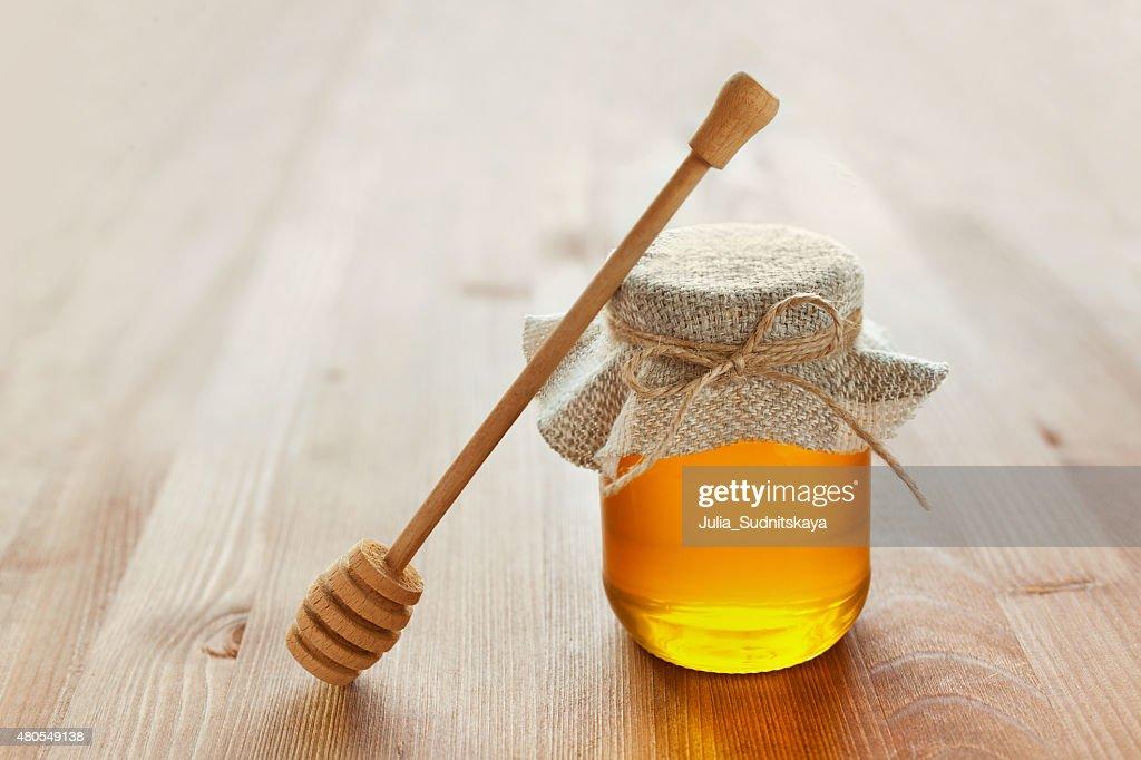 Miel en el recipiente con mallas sencillas, cuchara de miel, limón y jengibre : Foto de stock