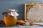Glass honey jar with bee pollen, honeycombs and lavender on a blue wooden table.