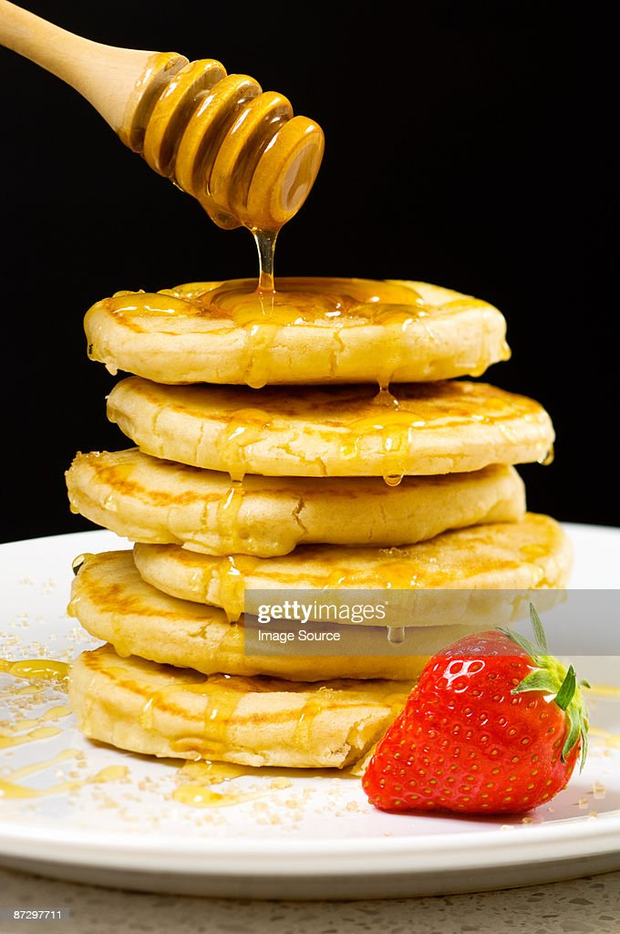 Honey pouring over pancakes : Stock Photo