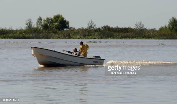 Honey producers Angel Dovico and Fernando Hinz sail the Parana river heading to harvest bee honey from their apiary in a island of the Parana Delta...