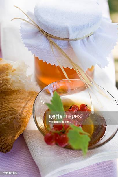 Honey, redcurrants and croissant on table in open air