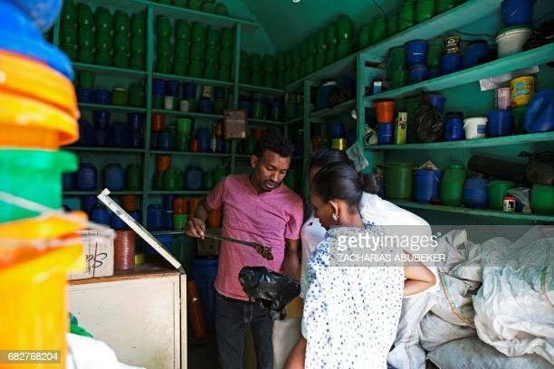 Honey shop keeper Haile Gebru is pictured preparing honey to be sold to customers in Mekelle in the Tigray region of northern Ethiopia on March 30...