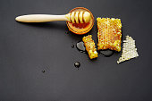 top view, honey bee flows out of honeycomb on a black background, wooden spoon for honey