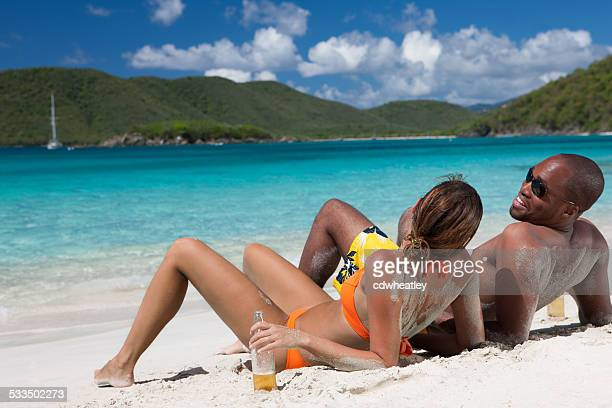 honeymoon couple drinking beers at a beach in St.John, USVI