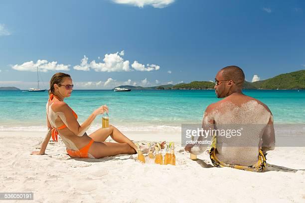 Flitterwochen Paar trinken eiskaltes Bier an einem tropischen Strand am Karibischen Meer