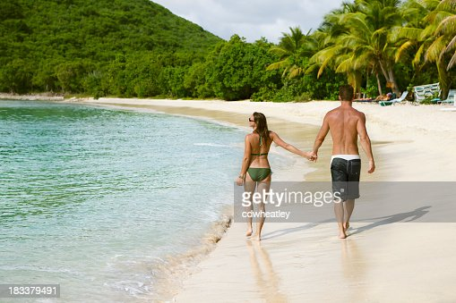 honeymoon couple holding hands and walking along a Caribbean beach