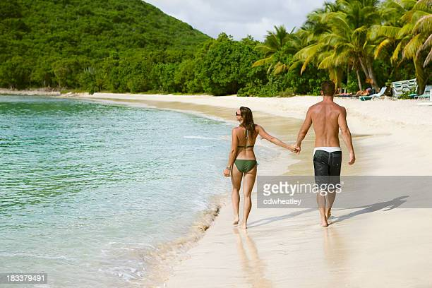 honeymoon couple holding hands and walking along a Caribbean beach