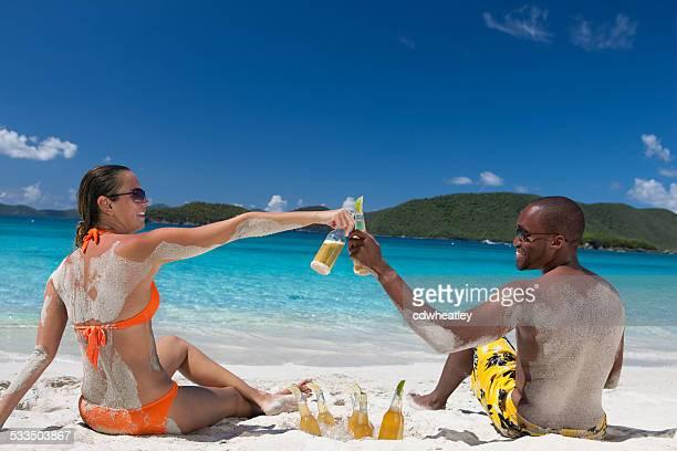 Flitterwochen Paar, die einen toast am Strand am Karibischen Meer
