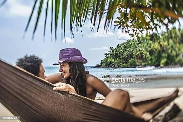 Honeymoon couple relaxing in hammock by the sea.
