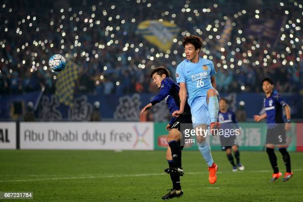Hong JeongHo of Jiangsu FC fights for the ball with Takagi Akito of Japan's Gamba Osaka during their AFC Champions League group stage football match...