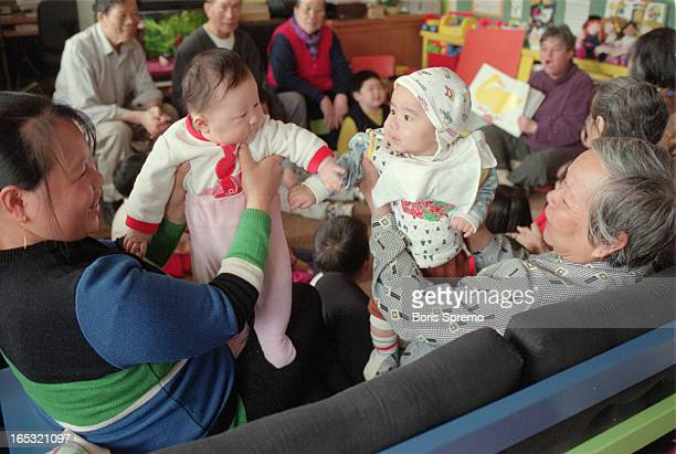 Hong Juan Yu with her daughter Shelley41/2month on left and grandmother Chau Yueh Wong with Fong Yip Wong5 month oldduring the program class Others...