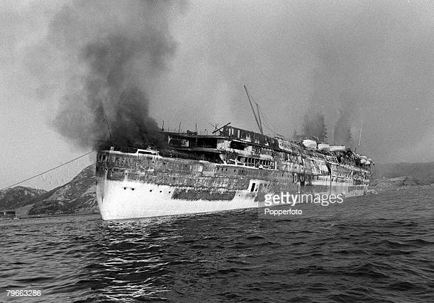 Hong Kong 11th January 1972 Smoke and fire engulf former British passenger liner 'RMS Queen Elizabeth' in Hong Kong where it was being fitted out as...