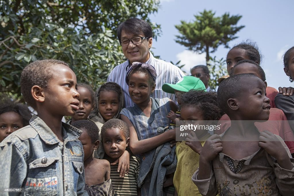 Hong Kong actor Jackie Chan poses with children as he visits a farm as part of the Purchase from Africans for Africa Programme (PAA), South-South Cooperation Project, in Hawassa on March 21, 2014. The PAA is an initiative launched by the Food and Agriculture Organisation of the United Nations (FAO), which aims to promote the buying of locally grown food in several parts of Africa. AFP PHOTO / ZACHARIAS ABUBEKER