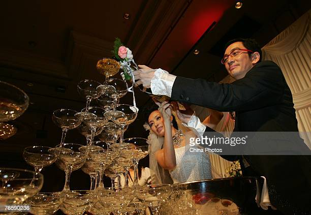 Hong Kong actor Lawrence Ng Kai Wah and his bride Shi Yangzi pour champagne into glasses during their wedding ceremony at the ShangriLa Hotel...