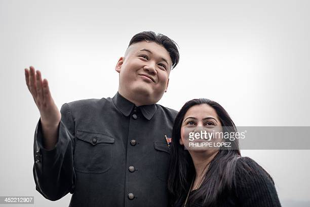 Hong Kong born Australian named Howard and impersonator of North Korean leader Kim JongUn poses with a tourist in Hong Kong on November 27 2013...