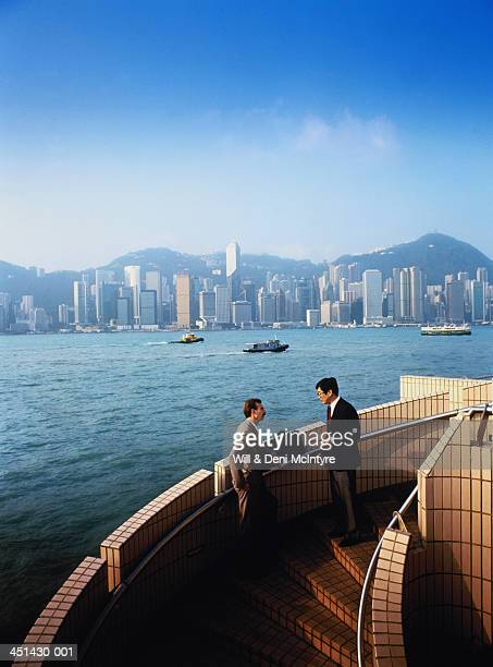 Hong Kong, business men talking on stairs overlooking harbour