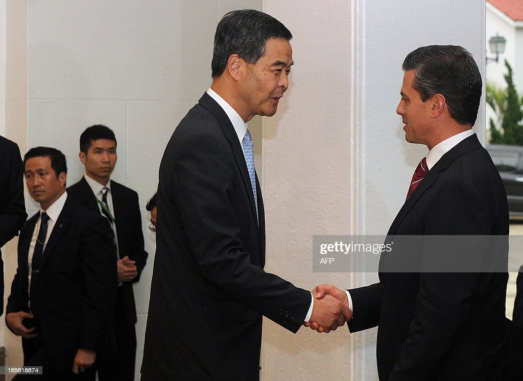 Hong Kong Chief Executive Leung Chun-Ying (C) shakes hands with Mexico's President Enrique Pena Nieto (R) before their meeting at Government House in Hong Kong on April 5, 2013. Enrique Pena Nieto arrived in Hong Kong on April 5 on a trip aimed at deepening economic ties and widening relations with the Asia-Pacific region. AFP PHOTO / POOL / Dale de la Rey