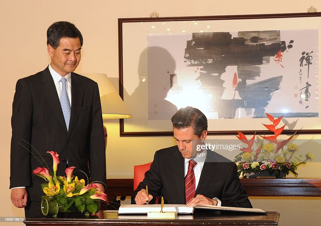 Hong Kong Chief Executive Leung Chun-Ying (L) watches as Mexico's President Enrique Pena Nieto (R) signs the guest book before their meeting at Government House in Hong Kong on April 5, 2013. Enrique Pena Nieto arrived in Hong Kong on April 5 on a trip aimed at deepening economic ties and widening relations with the Asia-Pacific region. AFP PHOTO / POOL / Dale de la Rey