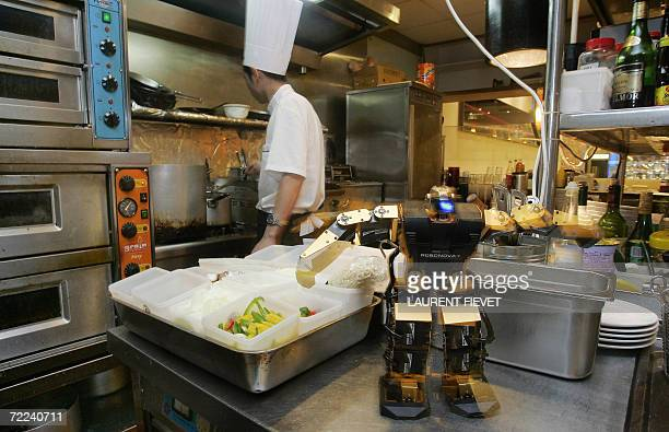 A robot performs preprogramed actions as a chef prepares food in the Robot Kitchen restaurant in Hong Kong 25 September 2006 With a whir and a flash...