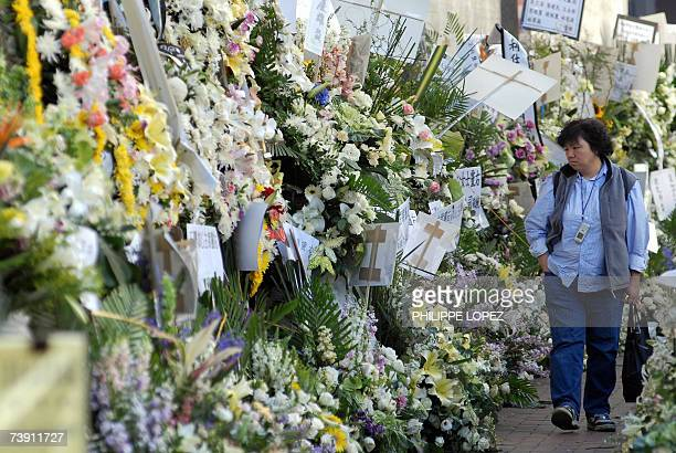 A woman walks along a sea of wreaths displayed outside a funeral house where the funeral of Nina Wang is being held in Hong Kong 18 April 2007 Asia's...