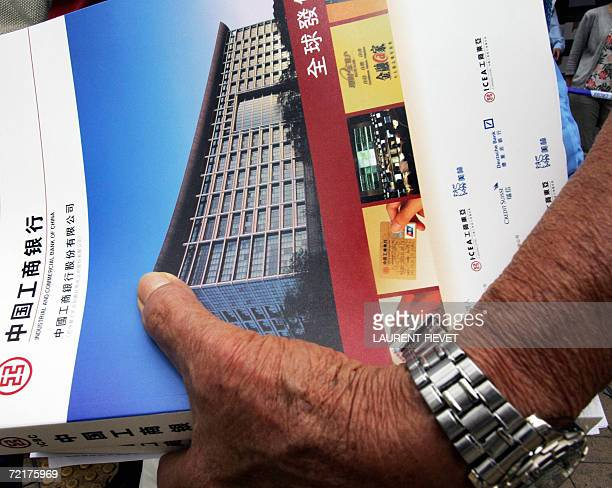 An elderly investor holds his application form and prospectus of the Industrial and Commercial Bank of China outside a bank in Hong Kong 16 October...