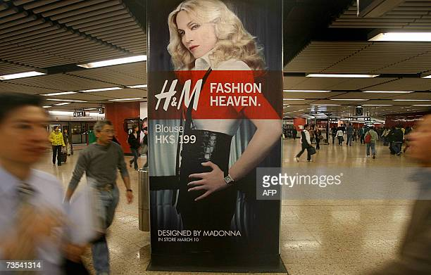 Commuters walk past a billboard showing Madonna at a station of the Central Mass Transit Rail System in Hong Kong 09 March 2007 HM will launch 10...