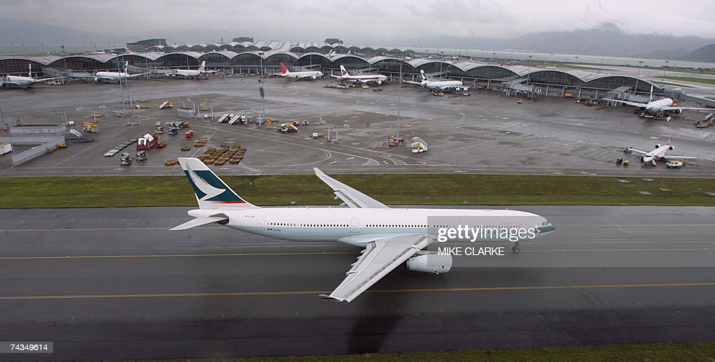 CORRECTION A Cathay Pacific plane taxis at Chek Lap Kok airport past the terminal in Hong Kong 22 May 2007 AFP PHOTO/POOL/MIKE CLARKE