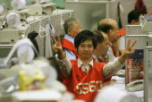 CORRECTION ADDITION OF INFORMATION A trader gives a victory salute after record highs at the Stock Exchange in Hong Kong 18 June 2007 Hong Kong share...