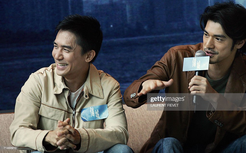Japanese-Taiwanese actor <a gi-track='captionPersonalityLinkClicked' href=/galleries/search?phrase=Takeshi+Kaneshiro&family=editorial&specificpeople=171924 ng-click='$event.stopPropagation()'>Takeshi Kaneshiro</a> (R) gestures while Hong Kong actor Tony Leung smiles during a press conference for the launch of their new movie 'confession of pain', in Hong Kong, 09 July 2006. AFP PHOTO / Laurent FIEVET