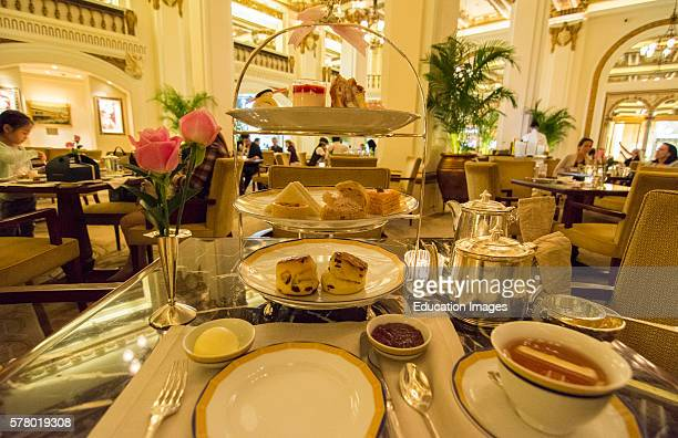 Hong Kong China Peninsula Hotel lobby exclusive High Tea with tea Afternoon Tea of cakes and finger sandwiches at table