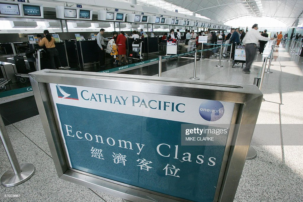 This file photo dated 09 March 2005 shows passengers waiting in the Cathay Pacific checkin queue at Hong Kong's Chek Lap Kok airport Hong Kong flag...