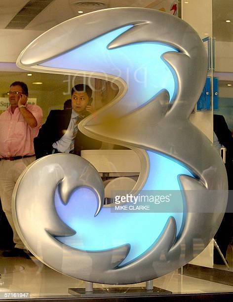 This file picture taken 15 October 2004 shows potential customers at a Hutchison Whampoa 3G shop checking out the latest 3G telephones Major blue...