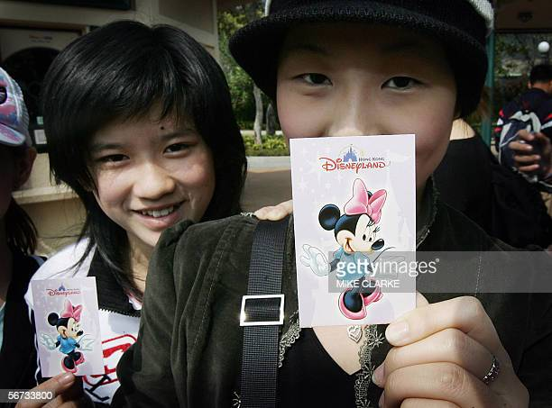 Two tourists from Malaysia pose with their just purchased theme park tickets outside the entrance to the Disneyland Amusement park in Hong Kong 03...