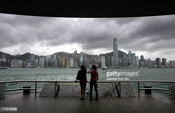 Two young women look at the stormy Hong Kong island skyline along Victoria Harbour 03 August 2006 as strong winds and rain lash the territory Typhoon...
