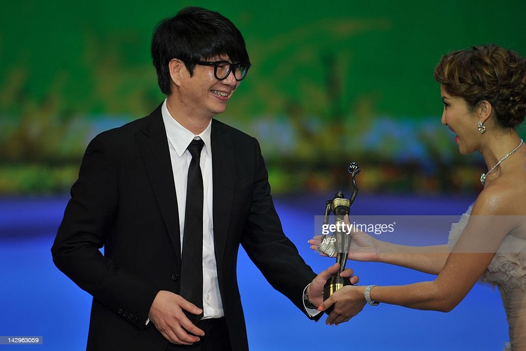 Hong Kong composer Chan Kwong Wing smiles as he receives the award for Best Original Film Score for the film 'Wu Xia', from Singer Coco Lee at the 31st Hong Kong Film Awards on April 15, 2012. The annual awards are the Hong Kong equivalent to the Oscars and the British BAFTAS.