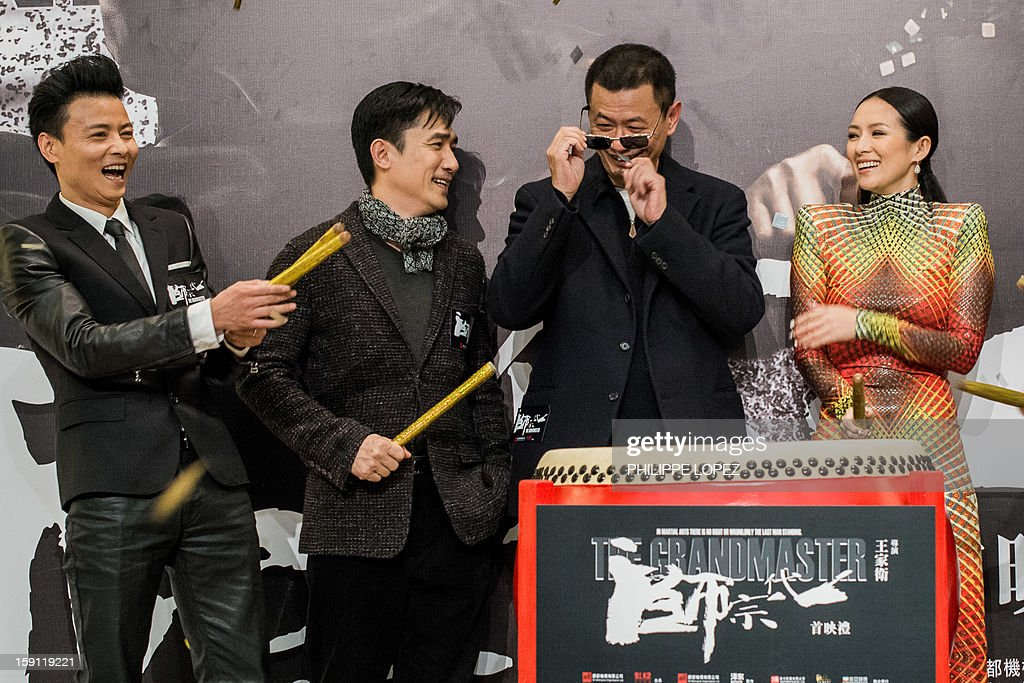 Hong Kong director Wong Kar Wai (C) removes confetti from his sunglasses after he beat the drum with cast members (L - R) Hong Kong actors Julian Cheung and Tony Leung, Chinese actress Zhang Ziyi to mark the Hong Kong premiere of his new film The Grandmaster' in Hong Kong on January 8, 2013. Wong Kar-wai's long awaited new film The Grandmaster, about battling martial artists, received its first public showing in the director's home city. AFP PHOTO / Philippe Lopez