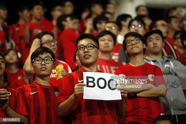A Hong Kong fan holds up a sign that reads 'Boo' while the national anthem was being played during a world cup qualifier at Mong Kok stadium in Hong...