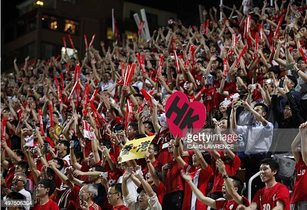 Hong Kong fans cheer after Hong Kong held China to a nil all draw at Mong Kok stadium in Hong Kong on November 17 2015 Hong Kong fans booed the...