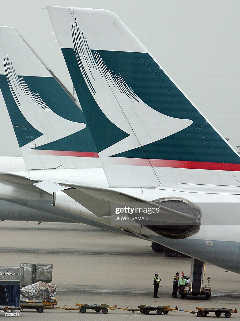 Ground staff wait under Cathay Pacific aircrafts at the Hong Kong International Airport in Hong Kong 21 February 2007 The Hong Kong based airline...