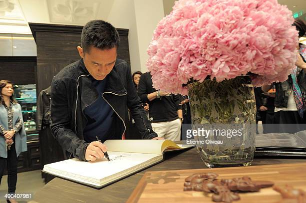 Hong Kong international actor Tony Leung signing the guest book during the Chrome Hearts Beijing Store Opening on May 14 2014 in Beijing China