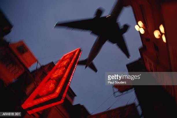 Hong Kong, Kowloon, passenger plane flying over neon sign at night