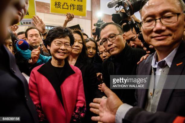 Hong Kong leadership hopeful Carrie Lam is surrounded by prodemocracy protestors and security as she prepares to speak to the media after submitting...