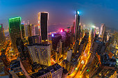 Aerial view of Hong Kong skyscrapers at night from Wooloomooloo Bar, located on rooftop of The Hennessy in Wan Chai, Hong Kong island. Fisheye view.
