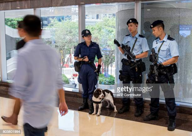 Hong Kong police stand with a police dog along an elevated walkway in Hong Kong on June 30 2017 as security has been ramped up for the visit of...